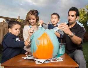 John Byrne/Tribune The Hess family of Spanish Springs applies teal-colored paint to a pumpkin for the Teal Pumpkin Project, which offers non-food treats at Halloween for children with food allergies. From left are Preston, 3; mother Erin Hess; Tyson, 6; and father Aaron Hess.