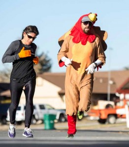 John Byrne/Tribune Ryan Hess, the Reed High School cross country coach (right), displays the Thanksgiving spirit while running Saturday in Mendive Middle School's inaugural Turkey Trot. The fundraising event featured a 1.5K fun run and a 5K run, with proceeds from registration fees going to the school's PTA to support academic programs.