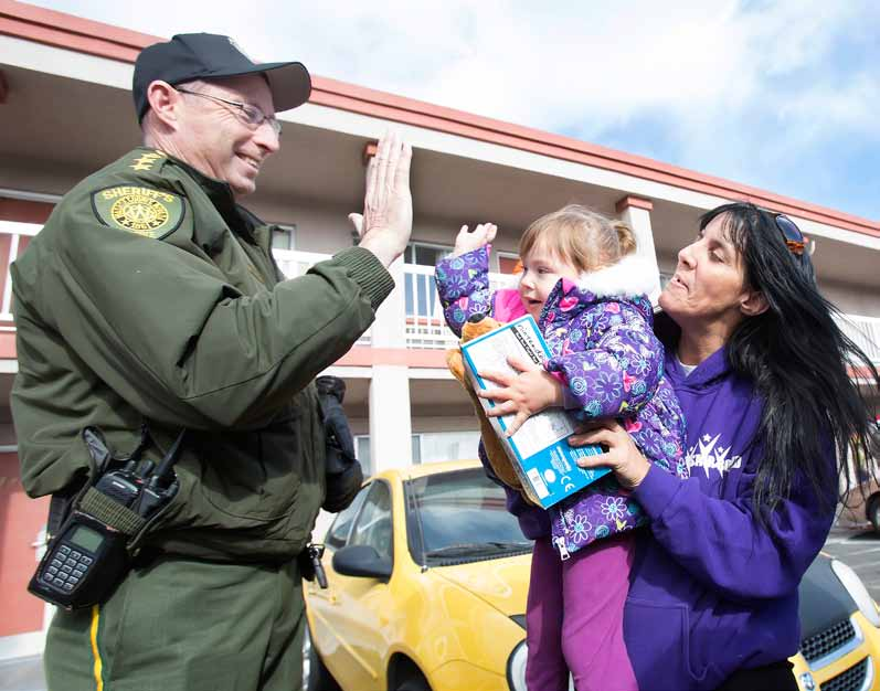 """John Byrne/Tribune Washoe County Sheriff Chuck Allen receives a high five from 2-year-old Marie Rhodes, who is being held by her grandmother, Tamara Rhodes, after the sheriff gave the girl a gift as part of Saturday's """"Christmas on the Corridor"""" caravan. The caravan featured Allen and Santa distributing gifts at motels and trailer parks in Reno's 4th, 5th and 6th Street corridor."""