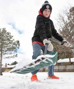 John Byrne/Tribune Adam Coley, 12, a sixth-grade student at Jerry Whitehead Elementary School, shovels snow at his home in Sparks the day before Christmas.