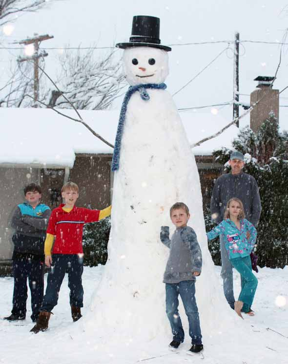 Courtesy photo Don Weaver and his children, with the help of neighbors, constructed a 10½-foot snowman in Sparks on Sunday by filling a trash can six times with snow and stacking the layers.  From left, Warren Jenkins, Gabriel Weaver, Rex Jenkins, Faith Weaver and Don Weaver (back) pose with the snowman.