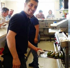 "Carlos ""Carlitos"" Martinez checks on his roasted poblano chiles, made daily at Carlitos Cocina Mexican Restaurant."