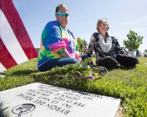 John Byrne/Tribune Sparks residents Tirzah Sneed (left) and Charlene Young (right) laid flowers at the grave site of family members Byron Young and his wife Joyce on Monday at the Northern Nevada Veterans Memorial Cemetery in Fernley. Byron, a Navy Veteran of World War II, was a 1940 era Sparks High School graduate. Thousands gathered for the Memorial Day ceremony where Nevada Governor Brian Sandoval delivered one of the keynote speeches. More photos on page 6.