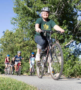 John Byrne/Tribune -  Vice President of the Sparks Kiwanis Club Ellen Jacobson leads a bike ride at Cottonwood Park on Saturday. The Riding on the River event featured games for the kids, bike decorating and a bike parade, all for free.
