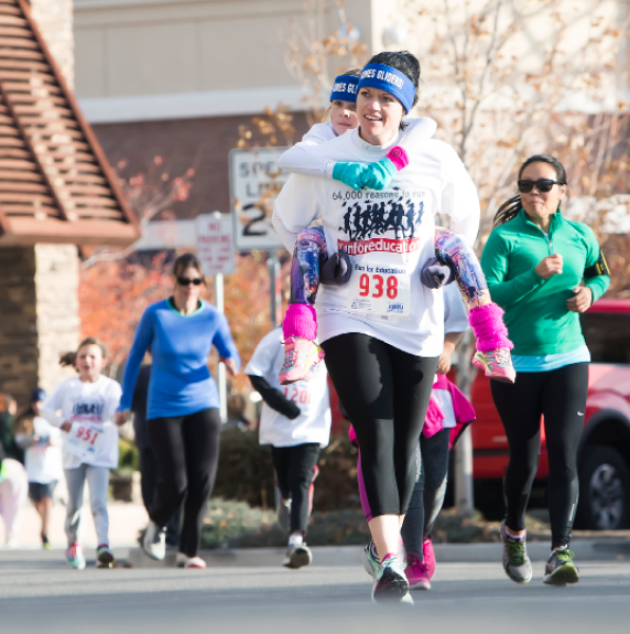 John Byrne photos/Tribune - (Above) Danielle Eaton, from Nancy Gomes Elementary School, carried an extra load across the finish line Saturday morning at the Run for Education in Sparks. The 10K event benefitted students from the Washoe County School District. (Left) Washoe County Board of Trustee Member Angie Taylor congratulated runners and handed out participation medals when they completed the race.
