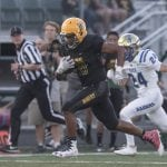 John Byrne photos/Tribune Bishop Manogue's Peyton Dixon escapes a Reed defender during the Raiders 50-7 loss Friday night. Dixon finished the game with 273 rushing yards and six touchdowns.